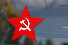 Estrella cinco-acentuada roja con el emblema de la hoz y del martillo imagenes de archivo