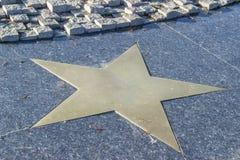 Estrella de bronce en el pavimento de mármol Imagen de archivo libre de regalías