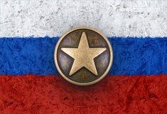 Estrella de bronce en la bandera rusa en fondo Imágenes de archivo libres de regalías