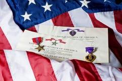 Estrella de bronce y corazón púrpura imagen de archivo