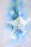 Estrella de dibujo con los fondos azules del bokeh para el día de la Navidad Imagen de archivo