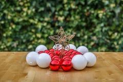 Estrella de la Navidad en el medio de las bolas blancas y rojas Foto de archivo libre de regalías