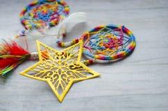 Estrella de oro a cielo abierto perforada en un fondo de madera gris Dreamcatcher con las plumas con las gotas coloreadas fotografía de archivo libre de regalías