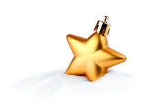 Estrella de oro de la Navidad en nieve Fotografía de archivo