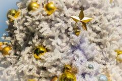 Estrella de oro y bolas de oro en la decoración blanca al aire libre del árbol de navidad Para el alero de la Navidad y la celebr Imagen de archivo libre de regalías