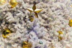 Estrella de oro y bolas de oro en la decoración blanca al aire libre del árbol de navidad Para el alero de la Navidad y la celebr Imagen de archivo