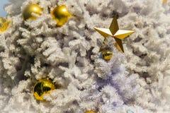 Estrella de oro y bolas de oro en la decoración blanca al aire libre del árbol de navidad Para el alero de la Navidad y la celebr Fotografía de archivo libre de regalías