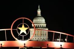 Estrella de Tejas con el edificio del capitolio del estado en la noche fotos de archivo