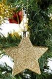 Estrella del oro de la Navidad en árbol Fotos de archivo