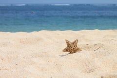 Estrella del oro en la arena Fotos de archivo