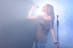 Estrella del rock rubia hermosa en el canto de la etapa Foto de archivo libre de regalías