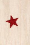 Estrella roja brillante de la Navidad en un fondo de madera Foto de archivo