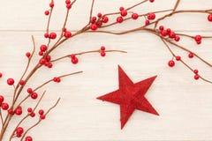 Estrella roja de la Navidad adornada con las bayas rojas Imagenes de archivo