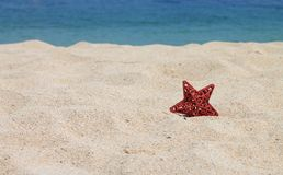 Estrella roja en la arena Imagen de archivo