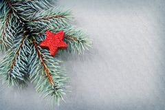 Estrella roja en la rama spruce verde aislada Fotos de archivo