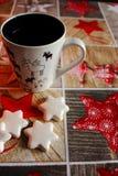 Estrellas blancas y taza de las galletas adornadas con los alces en mantel festivo con las estrellas y el modelo de madera Imagenes de archivo