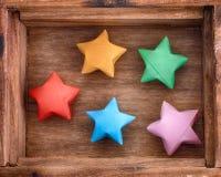 Estrellas de la suerte coloridas de la papiroflexia en una caja de madera Fotografía de archivo libre de regalías