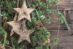Estrellas de las decoraciones de la Navidad y ramas de árbol de madera de pino Fotografía de archivo libre de regalías