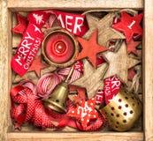 Estrellas de madera de las decoraciones de la caja de la Navidad, cintas rojas y burning Fotografía de archivo libre de regalías