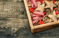 Estrellas de madera de las decoraciones de la Navidad y cintas rojas Foto de archivo libre de regalías