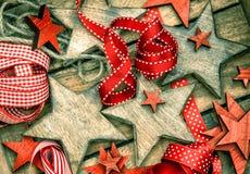 Estrellas de madera de las decoraciones de la Navidad y cintas rojas Imagen de archivo