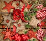 Estrellas de madera de las decoraciones de la Navidad y cintas rojas Imagenes de archivo