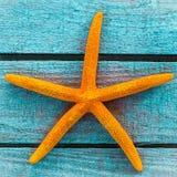 Estrellas de mar anaranjadas en los tableros de madera de la turquesa Foto de archivo libre de regalías