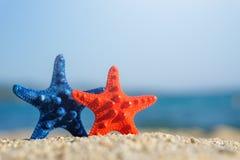 Estrellas de mar azules y rojas fijadas en la arena en la playa Mar azul en fondo imagenes de archivo