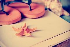 Estrellas de mar, balanceos y libro, filtrados Fotografía de archivo