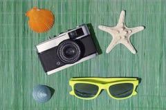 Estrellas de mar, cámara retra, gafas de sol, caracol de mar y cáscara del mar en la estera de bambú de la paja Foto de archivo