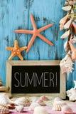 Estrellas de mar, cáscaras y verano del texto en una pizarra imagenes de archivo