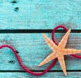 Estrellas de mar con la cuerda colocada en la madera de la turquesa Fotografía de archivo