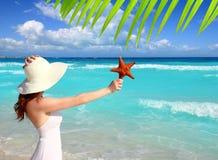 Estrellas de mar de la mujer del sombrero de la playa a disposición Fotos de archivo