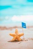 Estrellas de mar macras con la bandera del verano en la costa Imagenes de archivo