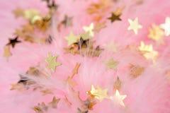 Estrellas de oro en un plumaje rosado Imagenes de archivo