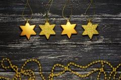 Estrellas de oro en un viejo fondo de madera negro La Navidad Foto de archivo