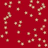 Estrellas del oro en fondo rojo fotografía de archivo