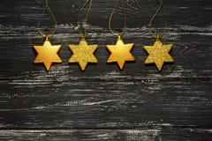 Estrellas del oro en una superficie de madera negra Fondo de la Navidad con el espacio para el texto Fotografía de archivo libre de regalías