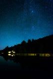 Estrellas en el cielo nocturno que refleja en Echo Lake, en la nación del Acadia Foto de archivo
