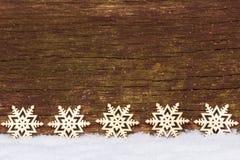 Estrellas en la nieve delante de la madera Fotografía de archivo libre de regalías