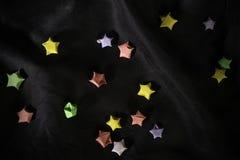 Estrellas multicoloras de la papiroflexia en el satén trasero Fotografía de archivo