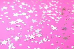 Estrellas plateadas de diversos tama?os en un fondo rosado fotos de archivo
