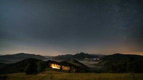 Estrellas que se mueven en cielo nocturno sobre las montañas y paisaje rural de niebla en el claro de luna Noche al tiro del carr almacen de video