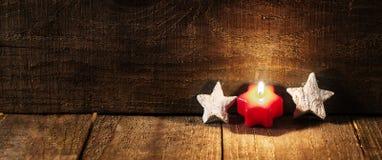 Estrellas rojas de la vela y del blanco en fondo de madera con el espacio de la copia Imágenes de archivo libres de regalías