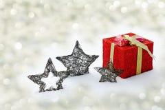 Estrellas rojas grandes del regalo de Navidad y de la Navidad en nieve que brilla Imagen de archivo
