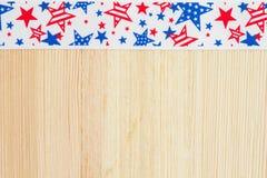 Estrellas rojas y azules en una cinta blanca en el fondo de madera Imágenes de archivo libres de regalías