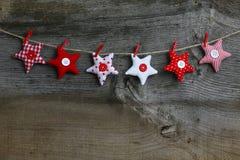 Estrellas rojas y blancas de la decoración de la ejecución de la Feliz Navidad de la tela Fotos de archivo