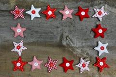 Estrellas rojas y blancas de la decoración de la Feliz Navidad de la tela en rústico Imagen de archivo