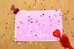 estrellas sparlking coloridas, corazones con la pluma roja y lunas en el papel rosado y el fondo amarillo Imagenes de archivo