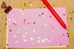 estrellas sparlking coloridas, corazones con la pluma roja y lunas en el papel rosado y el fondo amarillo Imágenes de archivo libres de regalías